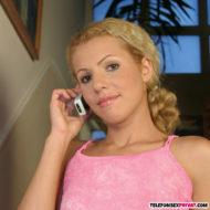 Junge blonde Studentin mit Zopf im rosa Kleid am Telefon