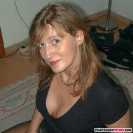 Reife Frau über 50 mit tiefen Ausschnitt hockt auf dem Boden