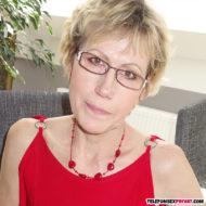 Reife Dame mit kurzen blonden Haaren und Brille im roten luftigen Oberteil