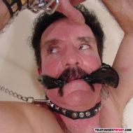 Schwuler Mann nackt mit festgeketteten Armen, Halsband und Knebel im Mund